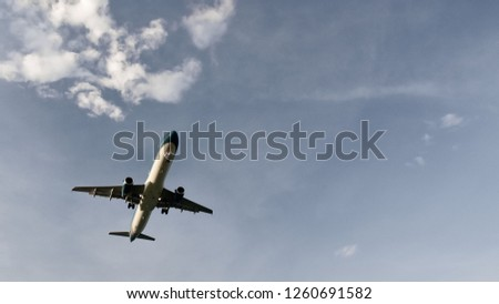 Atmospheric photo of an airplane flying across the blue sky past the clouds . Copy space fot text