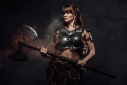 Atmospheric portrait of scandinavian amazon with brown hairs dressed in light armour holding two handed axe in dark background.