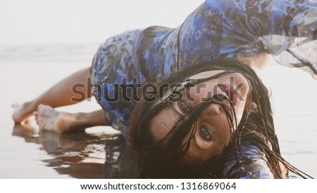 Atmospheric portrait of young wet woman in wet dress and with wet hair lying at sandy beach and looking at camera, close-up