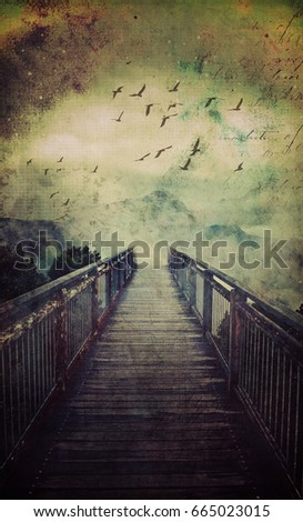 Atmospheric scene of a wooden bridge leading into low clouds above misty mountains