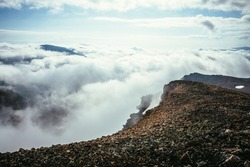 Atmospheric scenery on top of mountain ridge above clouds to vertex in thick low clouds. Minimalist view from precipice edge over clouds. Beautiful landscape with mountain range over dense clouds.