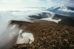 Atmospheric scenery on top of mountain ridge above thick low clouds. Scenic view from precipice edge over clouds to snowy mountains. Beautiful alpine landscape with mountain range over dense clouds.