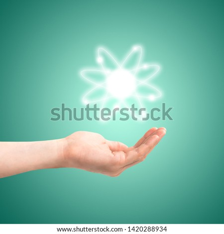 Atom structure model in a hand with nucleus and electrons, technological concept of nuclear power. Flat illustration on green background #1420288934