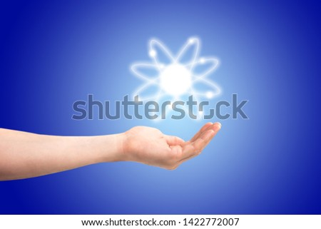 Atom structure model in a hand with nucleus and electrons, technological concept of nuclear power. Flat illustration on blue background #1422772007