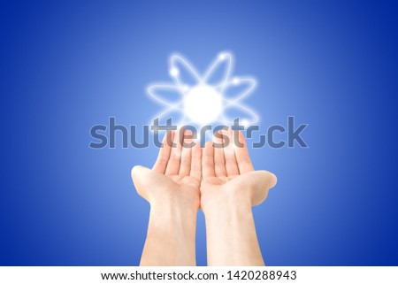 Atom structure model in hands with nucleus and electrons, technological concept of nuclear power. Flat illustration on blue background #1420288943