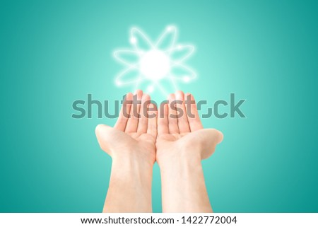Atom structure model in hands with nucleus and electrons, technological concept of nuclear power. Flat illustration on green background #1422772004