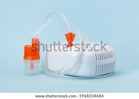 Atomizing cup with nebulizer mouthpiece for compressor inhaler on blue background. Medical equipment for inhalation therapy for asthma and respiratory diseases. Сток-фото ©