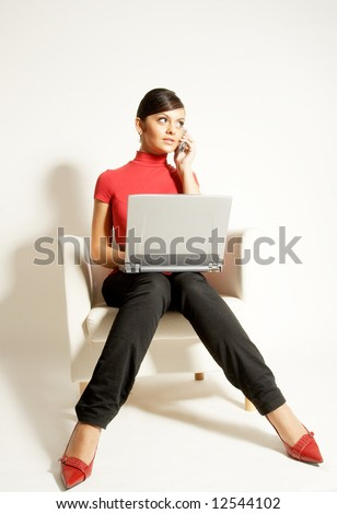 Atractive brunet businesswoman sitting with Laptop and phone on the white chair