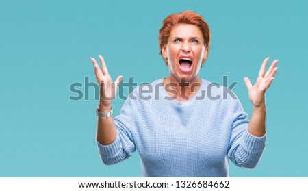 Atrractive senior caucasian redhead woman over isolated background crazy and mad shouting and yelling with aggressive expression and arms raised. Frustration concept. #1326684662