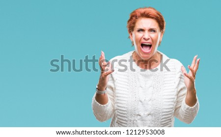 Atrractive senior caucasian redhead woman wearing winter sweater over isolated background crazy and mad shouting and yelling with aggressive expression and arms raised. Frustration concept.