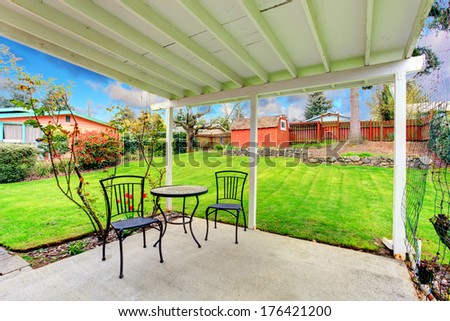 Attached pergola with patio table set overlooking beautiful green lawn, trees and red wooden shed
