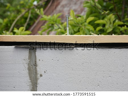 Attaching, installing wood board or plank on gas concrete blocks using masonry concrete screw, concrete fastener with a plastic anchor.