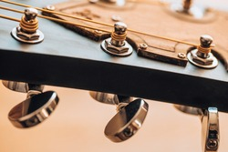 Attaching the strings to the fretboard - tuning the guitar - close-up of the tuning machine