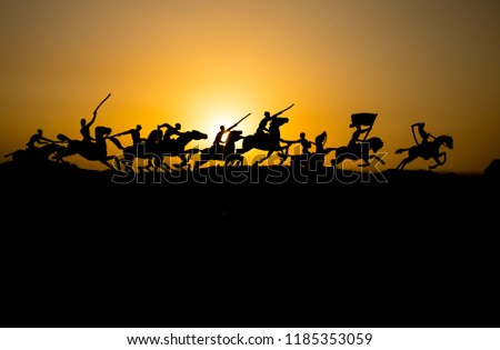 Attacking scene. War concept. Riders on horse ready to fight and soldiers on a dark foggy toned sunset background. Battle scene battlefield of fighting soldiers. Selective focus #1185353059