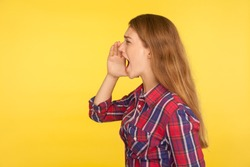 Attention, advertising! Side view of girl in checkered shirt holding palm near mouth and shouting loudly, screaming, proclaiming message, crazy news. indoor studio shot isolated on yellow background
