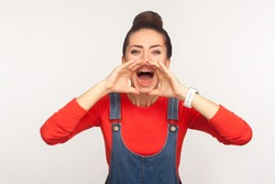 Attention, announcement! Portrait of stylish girl with hair bun in denim overalls holding arms near wide open mouth and screaming message, loud advertising. studio shot isolated on white background