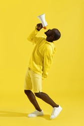 Attention! Black man shouting in megaphone on yellow background. Happy young male model screaming in loud speaker in studio