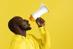Attention! Black man shouting in megaphone on yellow background portrait. Happy young male model screaming in loud speaker in studio