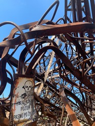 Attention! Danger to life. A dump of rusty scrap metal in an abandoned factory. Steam punk subculture. Degradation and decline of industry. Scrap iron. Scenic rust trash. Blue sky. Corrosion of metal.