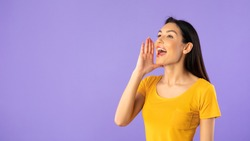 Attention, People. Portrait of happy female model holding hand near mouth, screaming aside at copy space isolated over purple studio background. Lady making offer yelling to free space, banner,