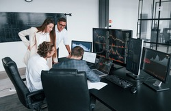 Attention to details. Team of stockbrokers works in modern office with many display screens.