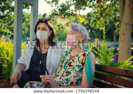 Attentive caregiver or companion and a senior adult woman in protective masks are sitting on a park bench. Summer sunny day. Stockfoto ©