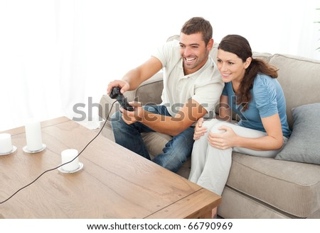 Attentive couple playing video game together in the living room at home