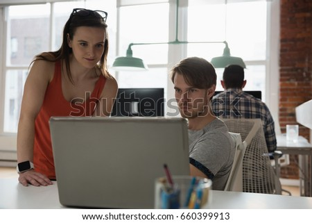 Attentive executives discussing over laptop in office #660399913