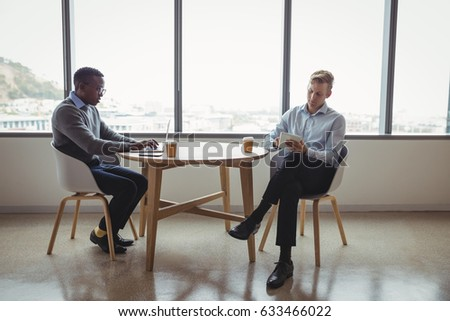 Attentive executives using digital tablet at table in office