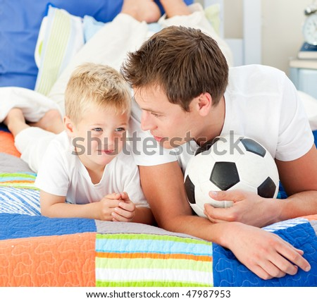 Attentive father and his son playing with a soccer ball lying on bed