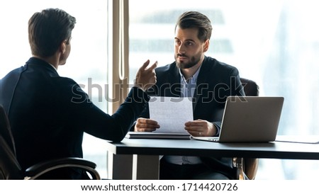 Attentive hr manager listening to candidate answering questions on job interview, serious focused recruiter holding cv, looking at applicant, sitting at desk in office, colleagues discussing project