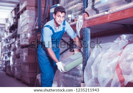 attentive male in uniform is choosing cement in the building store room