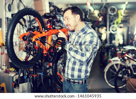 attentive male mounts bicycle parts for assembly bike in sports shop #1461045935