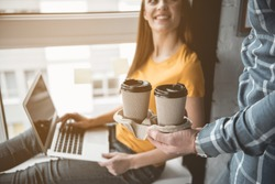 Attentive male person giving coffee to his female friend. Focus on paper cups