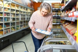 Attentive middle aged woman buying packed frozen cut fish at grocery store