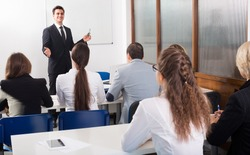 Attentive students with teacher in classroom at business training