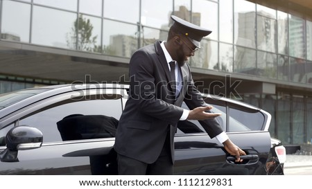 Attentive taxi driver politely opening car door, inviting client to sit down