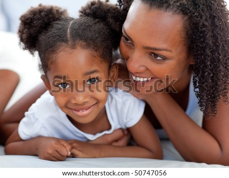 Attentive woman and her daughter relaxing lying down on bed at home - stock photo