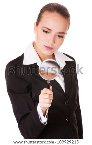 Attentive young business woman looking into a magnifying glass isolated on white background