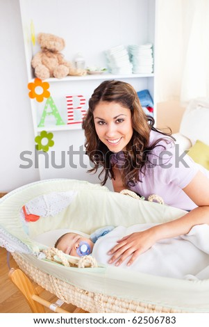 Attentive young mother taking care of her adorable baby at home