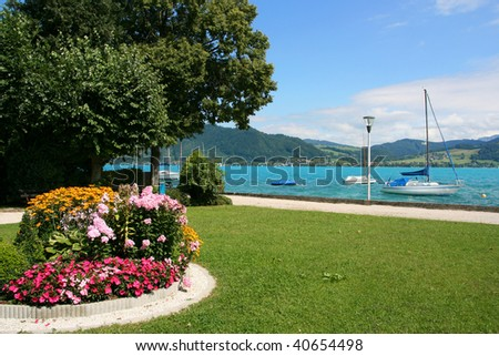 Attersee, lake in Salzkammergut, Austria. Flower bed and anchored boats.