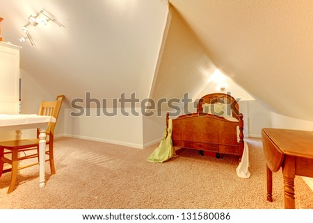Attic bedroom with desk and small bed.
