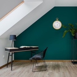 Attic home office room with simple desk and chair and big golden clock on emerald green wall