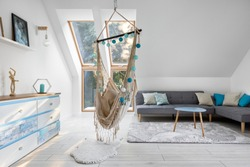 Attic room in white and blue with hammock seat, gray corner sofa and colorful chest of drawers