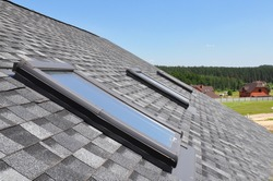 Attic skylight. Asphalt Shingles House Roofing Construction with Attic Roof windows, skylights waterproofing.