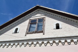 Attic window vent on old white brick, old house in Belarus, with blue sky background