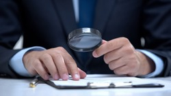 Attorney reading document with magnifier, studying case in detail, investigation