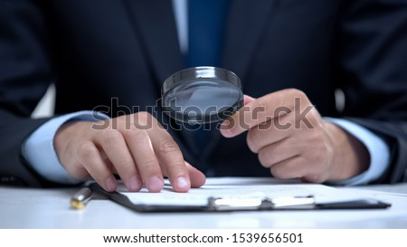 Attorney reading document with magnifier, studying case in detail, investigation Foto d'archivio ©