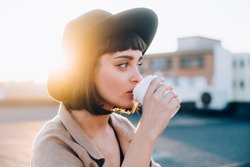 Attractive adorable woman with natural makeup sips on coffee in early morning on sunrise or sunset with light leaks, from to go cup, wears hipster fedora hat