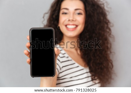 Attractive adult girl with ring in nose demonstrating her mobile phone on camera advertising new model, being glad while isolated against grey wall